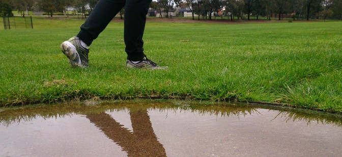 A flooded shotput circle with a persons legs in the forground reflected in the puddle